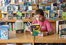Elementary aged girl reading book in school library