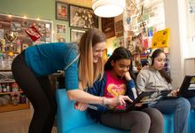 A sixth-grade English teacher helps two students during Sutton Middle School's International Baccalaureate immersion day