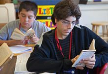 Eighth graders read books in while sitting their desks in class