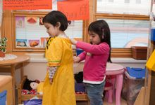 One girl helps another girl in pre-school class.