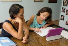 Mother helping daughter with remote learning lesson at their kitchen table