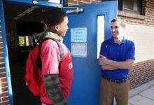 Teacher talks to high school student at his classroom door