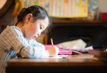 Elementary-aged girl writes on paper at home