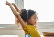 Elementary-aged girl stretches while sitting at her desk in her classroom
