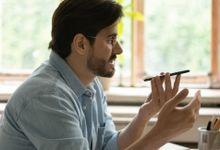 Man talks on his smartphone using the speakerphone