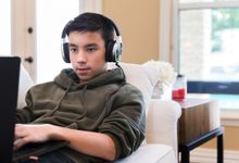 Teenage boy with headphones on couch on laptop