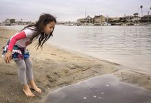 Girl looking into puddle on beach