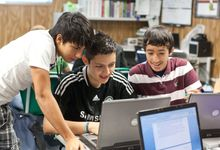 Middle school students work on a laptop together in their classroom