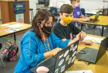 Teacher helps student working on Chromebook while wearing masks