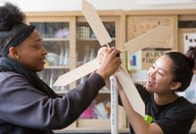 Two high school students work on science project designing wind turbine