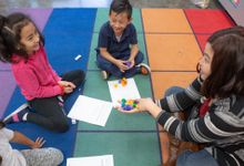 Elementary teacher works on a math assignment with children during circle time