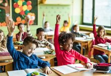 Elementary school students in classroom with hands raised