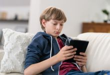 Middle school aged boy reading on tablet at home