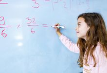 Elementary aged girl does math problem on whiteboard