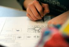 A closeup of a student's hand drawing flowers on a piece of paper with pen.