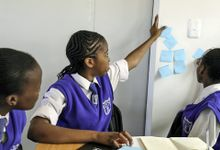 Three students wearing white collared shirts with a purple tie and vest are looking up toward the same direction. One of them is raising their hand, and another is putting a blue Post-It on the wall next to other blue Post-Its with writing on them.