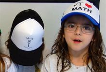 """Three young girls are standing beside each other wearing hats that say, """"I heart math."""""""