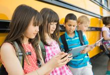 Five young students are leaning against a bus all looking at mobile devices.