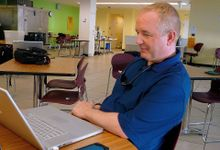 A teacher is sitting at a small table, smiling at his laptop. His cell phone is beside him on the table, connected to his laptop.