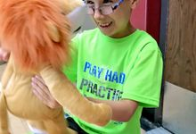 A young boy in a bright green shirt and glasses is smiling, holding a stuffed lion doll, looking straight into its face