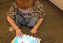 A young boy is squatting on a carpet, playing a game on a tablet.