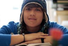 A closeup of a teenage student in a blue sweater and beanie sitting, arms folded over a book.