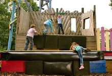 Four children climbing on a play structure