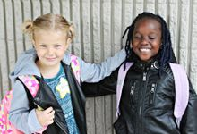 Two elementary school girls are smiling and standing side by side.