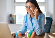A young female teacher wearing glasses is at her desk smiling and on the phone.