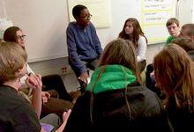 Boy on stool teaching engaged classmates circled around him