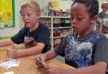 Two boys at a table looking at cards printed with various items to determine want versus need