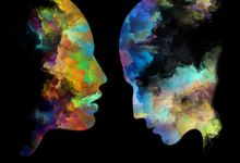 Two colorful heads made of paint against a black backdrop are facing each other.