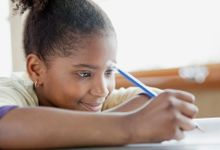 A young girl sits at her desk, writing with a pencil.