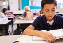 Children in a classroom read texts in books and tablet computers.