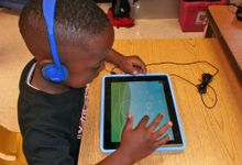 A bird eye's view of a young boy sitting at his classroom desk with blue headphones on, playing a game on a blue tablet.