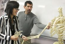 Girl and teacher looking at a human skeleton.