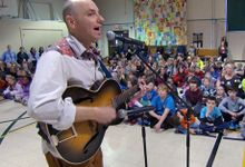 Man singing and playing the guitar in the gym full of students and teachers