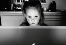 Young girl sitting at a table looking intently at something on a laptop