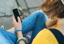 Photo of young person looking down at smartphone