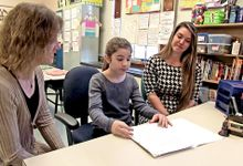 Student sharing her work with a teacher and a parent