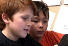 Two boys looking at a tablet