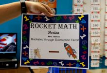 Teacher holding up Dorian's Rocket Math certificate that says he rocketed through subtraction facts