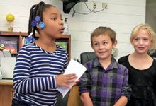 Children smile as one of their peers makes a presentation.