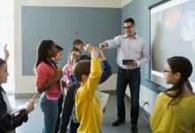 A male teacher and eight young students are standing in a blue-walled classroom near a projector with planets displayed on it.