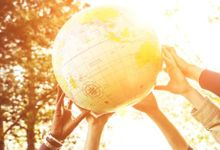 Many hands lifting up a large beach ball that looks like a globe