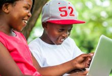 Girl and boy looking at a tablet smiling