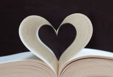 Photo of an open book with two pages curled to resemble a heart