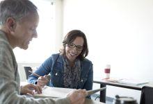 An instructional coach and a teacher discuss some paperwork.