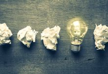 Four crumpled balls of paper and a lit light bulb illustrate the idea that success comes after failures.