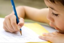 A young student is seen very close up writing on a sheet of paper with a pencil.